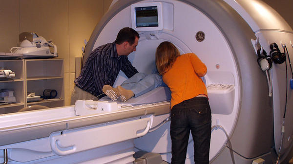 Dr. Amit Etkin and a research assistant help a participant into the bore of the MRI.