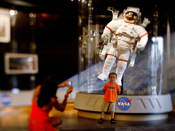 A child poses for a picture in front of an astronaut space suit at the Kennedy Space Center on the eve of the launch of Space Shuttle Endeavour July 14, 2009 in Cape Canaveral, Fla.