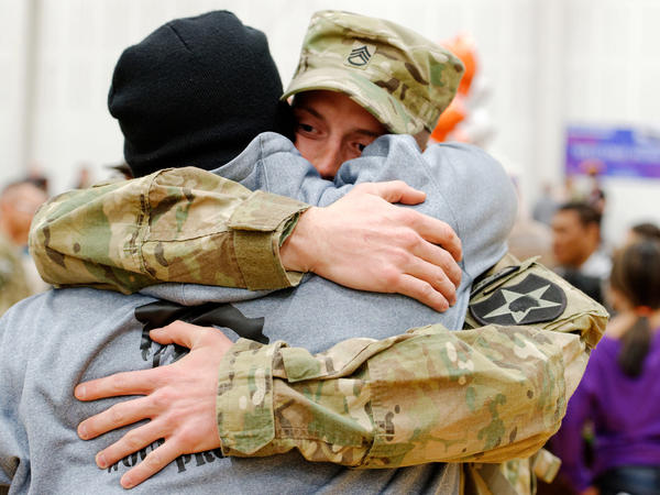As family and friends welcome the returning soldiers, Staff Sgt. Michael Blair gives Jeffries a bear hug.