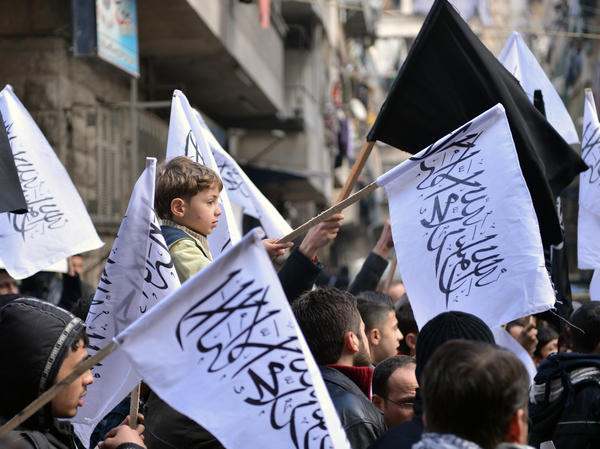 Supporters of the opposition Islamist group Al-Nusra wave their black-and-white flags during an anti-government demonstration earlier this month in the northern Syrian city of Aleppo.