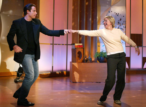 John Travolta dances with DeGeneres during a taping of her talk show in 2004.