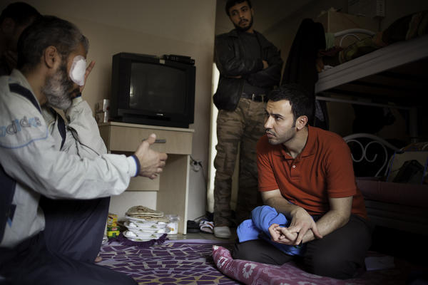 Mulham al-Jundi (right), who works for the nongovernmental organization Watan, visits an injured fighter at a recovery home for Free Syrian Army veterans. Jundi is one of the young Syrian humanitarian workers based in Reyhanli, Turkey, near the Syrian border.