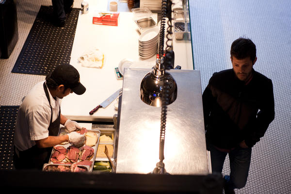 Nick Wiseman, partner at DGS Delicatessen, inspects the kitchen as an employee prepares pastrami sandwiches for lunch.