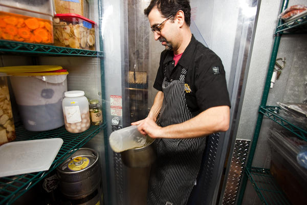 """Koslow grabs ingredients from the walk-in refrigerator that houses all of the deli's pickled vegetables and smoked meat. """"We'll pickle anything,"""" he says."""