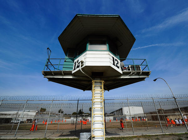 Inmates file by a guard tower at California's Chino State Prison in 2010.
