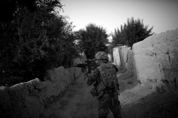 A soldier from the 4th Battalion, 9th Infantry Regiment, Manchus, looks toward the tree line through his rifle scope while on a foot patrol to visit Afghan Local Police in the Panjwai District of Kandahar province in southern Afghanistan. Panjwai is one of the most dangerous districts in Afghanistan.