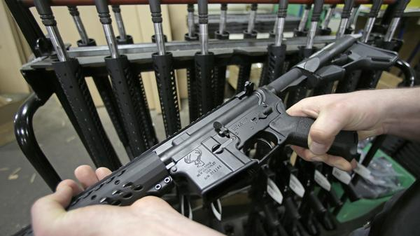 Veetek Witkowski holds a newly assembled AR-15 rifle at the Stag Arms company in New Britain, Conn., in April.