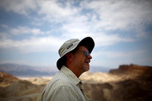 Charlie Callagan, a Death Valley National Park Ranger, stands near the bluffs overlooking Badwater Basin. Tourists come to experience temperatures they can't back home, Callagan says.