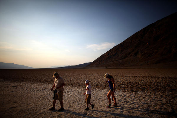 Tourists walk across the Badwater Basin which sits 282 feet below sea level, in Death Valley, Calif., on June 30. People from around the world flock to the area to experience temperatures that rise to the high 120's on a regular basis.