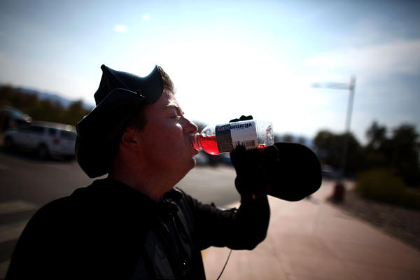 "Jonathan Rice, dressed as Darth Vader, gulps down a bottle of Vitamin Water after running a 6:36 mile in the hottest stretch of Death Valley. Rice has been doing the run to try and set a world record for the fastest mile run in a record-setting temperature and has dubbed it the ""Darth Valley Challenge."""