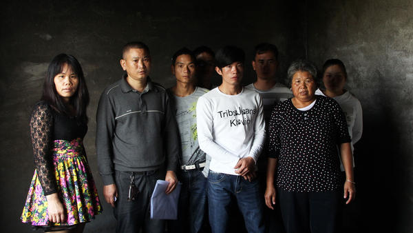 He's family members stand in the room where he self-immolated in late September. He's brother, Waiqing (second from left), says local officials have too much power and villagers can do nothing to stop the demolition of their homes.