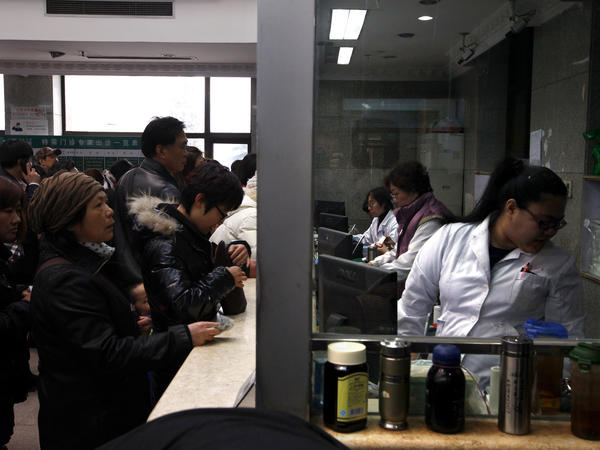 People wait in line at a counter for medical services at the Guanganmen Chinese medicine hospital in Beijing.