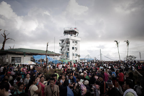 "Typhoon victims wait at an airport to leave Tacloban. A fight for ""sheer survival"" is underway as more than 220,000 people search for food, water and other essentials in Tacloban, NPR's Anthony Kuhn said Wednesday on <em>Morning Edition</em>."