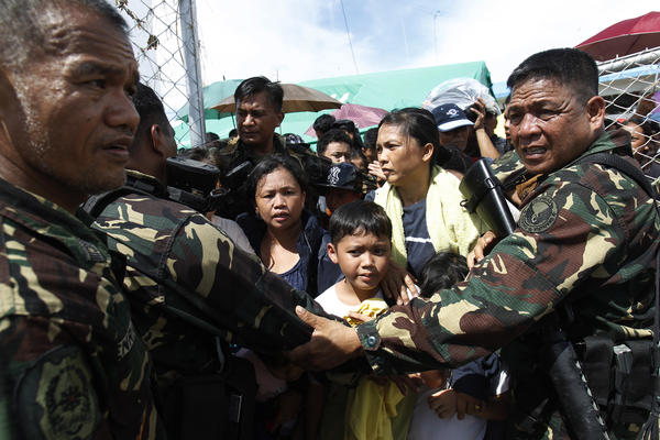 Soldiers hold back people who are waiting to board a military aircraft in Tacloban. While the government, international aid groups and foreign militaries have rushed to the affected area, they are having trouble getting to the victims because of blocked roads, the U.S. commander on the scene told NPR early Wednesday.