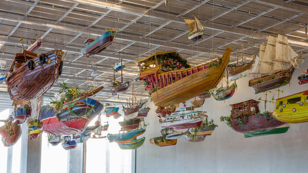 The boats of <em>For Those in Peril on the Sea,</em> by artist Hew Locke, hang in the entrance hall of the Perez Art Museum Miami, which opens this week.