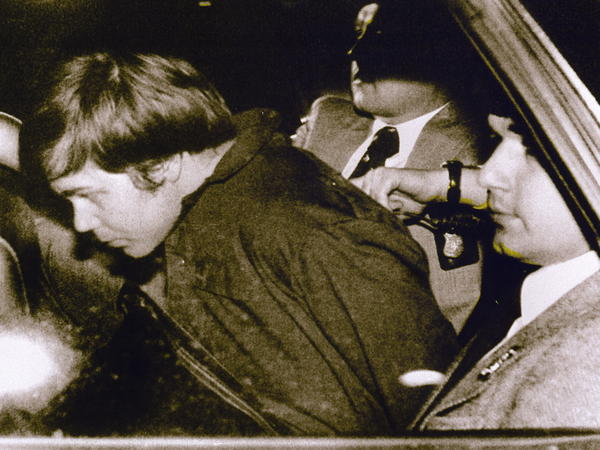 John Hinckley Jr. is escorted by police in March 1981 following his arrest after shooting then-President Ronald Reagan.