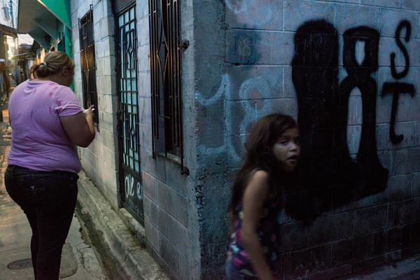 Mother and daughter hang around the streets of a residential area in San Salvador controlled by the gang Barrio 18.