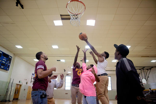 Mentor Marcus Taylor (left) plays basketball with Renaissance Academy High School students during gym class Oct. 8 in Baltimore.