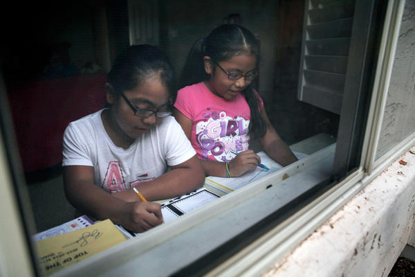 Vanessa Minero Leon (right) and her older sister, Lizette, work on their homework after school. Vanessa is in the gifted program at her elementary school in Arizona.