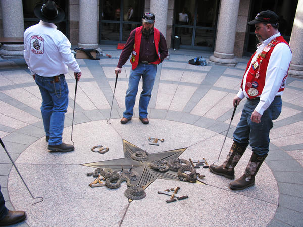 Sweetwater Jaycees surrounding rattlesnakes on Diamondback Day at the Texas state Capitol.