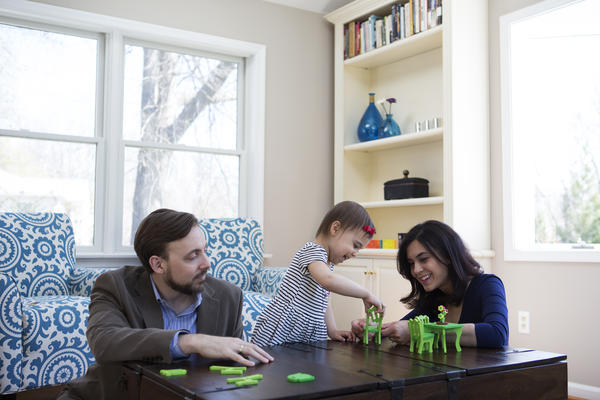 Travis and Sadiye Rieder play with Sinem in their home. They've agreed that if they want more children, they'll adopt.