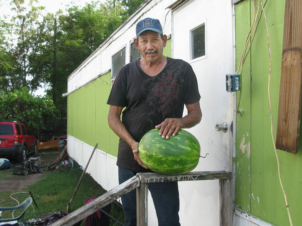 Justino DeLeon, 58, stands in front of his home in Pharr, Texas. A former watermelon picker; he retired from farm work when he fell off a melon truck and hurt his arm.