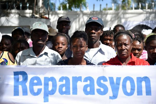 Haitians protest in front of a U.N. office on Oct. 15, 2015, demanding reparations for families of people who suffered or died from cholera. The outbreak started in 2010, claiming some 9,000 lives.