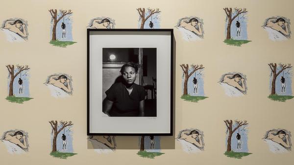 Noah Davis hung a 1949 portrait of the wife of a lynching victim on top of Robert Grober's 1989 <em>Hanging Man/Sleeping Man</em> screen-printed wallpaper.