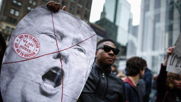 A man holds a sign as he takes part in a protest against Republican presidential front-runner Donald Trump in New York on March 19.