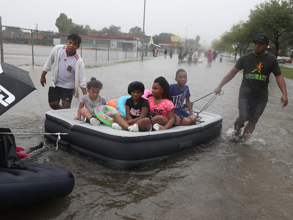 Children on an air mattress are towed down a flooded street in Houston on Sunday.