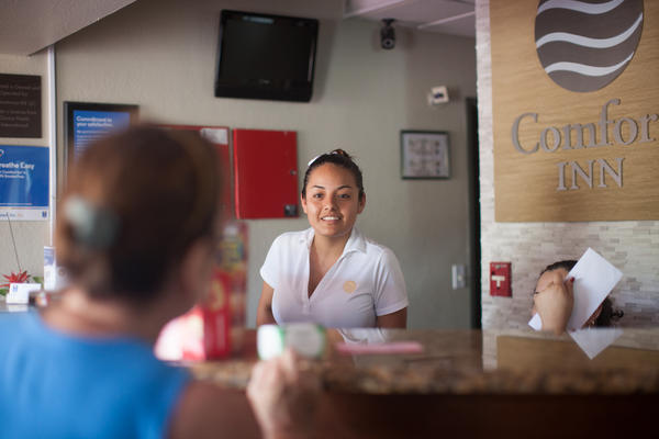 Flor Garcia talks to a guest at the Comfort Inn in Fort Myers, Fla. The hotel has become a second home for local residents who find themselves evacuating there during hurricanes.