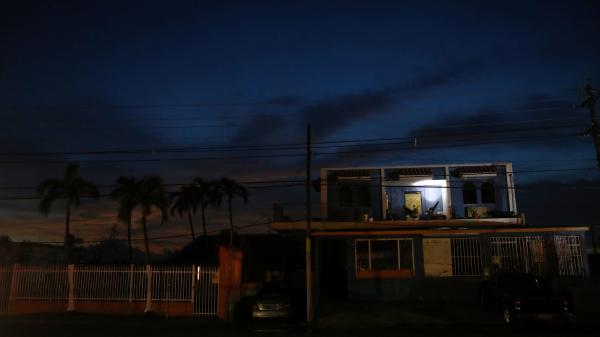 A man rests in a hammock, using a battery-operated light, in an area of San Isidro without electricity more than two weeks after Hurricane Maria hit the island of Puerto Rico.