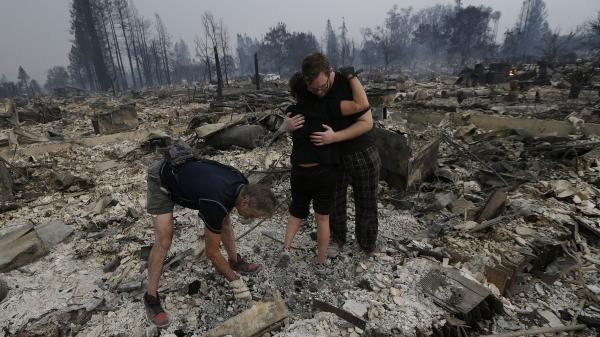 Michael Pond, left, looks through ashes as his wife Kristine, center, gets a hug from Zack Thurston, their daughter's boyfriend, while they search the remains of their home destroyed by fires in Santa Rosa, California.