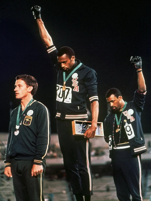 """At the 1968 Olympics, U.S. athletes Tommie Smith (center) and John Carlos protested during the playing of """"The Star-Spangled Banner"""" after Smith received the gold and Carlos the bronze medal in the 200 meter run."""