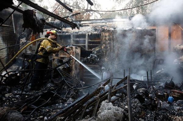 <p>Firefighter Nick Gonzalez-Pomo of the San Rafael Fire Department waters down smoldering ashes on a garage Tuesday, Oct. 10, 2017, in Napa, California. Wildfires whipped by powerful winds swept through the California wine country sending thousands fleeing as flames rage unchecked through high-end resorts, grocery stores and tree-lined neighborhoods.</p>