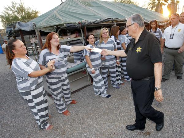 "Maricopa County Sheriff Joe Arpaio signs autographs for inmates as he walks through  ""Tent City"" in Phoenix in 2012."