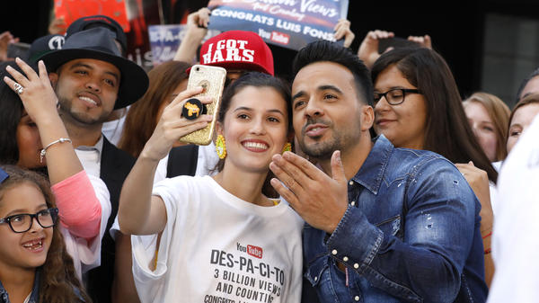 """Luis Fonsi taking a selfie with a fan wearing a shirt touting the YouTube success of """"Despacito,"""" his global hit with Daddy Yankee."""