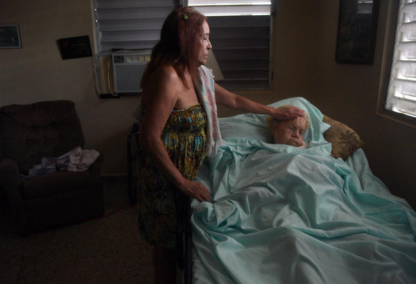 Floodwaters seep into home of 97-year-old Margarita Maestre on Avenida Esteves. She is bedridden with respiratory issues and a feeding tube, with caregiving provided by her daughter Blanco Matos, weary from concerns about her medical needs and the inability to get her out in emergency.
