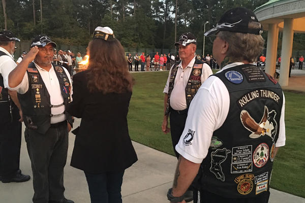 Members of the Jacksonville, N.C. Rolling Thunder chapter pass a flame during a cememony honoring prisoners of war and troops missing in action.