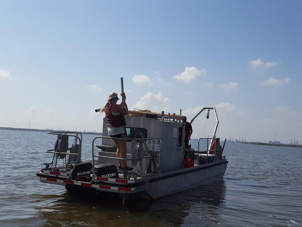 Lindsay Cristides, a master's student in oceanography at Texas A&M University, anchors a research vessel in the Houston Ship Channel before taking samples of sediment left behind by Hurricane Harvey floods. The samples will be tested for contaminants including heavy metals.