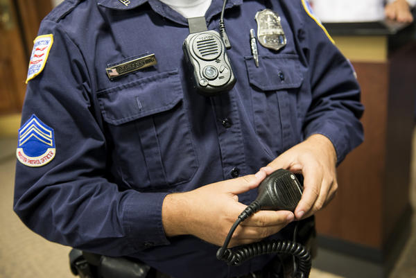 D.C. Master Patrol Officer Benjamin Fettering shows a body camera worn in place of a normal radio microphone before a news conference in 2014.
