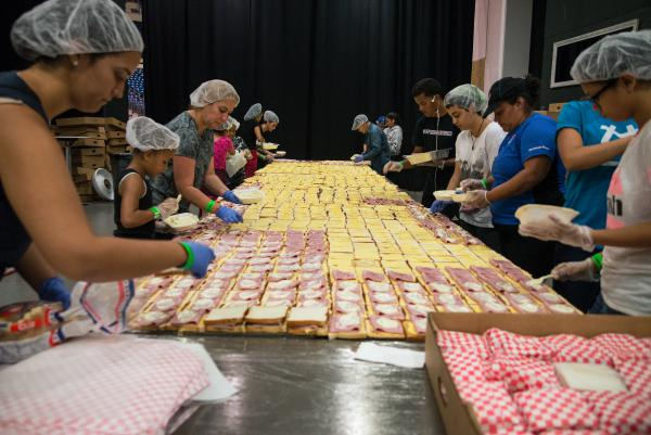 "Volunteers assemble tens of thousands of sandwiches each day at the Coliseo in San Juan, Puerto Rico. Chef José Andrés, who is overseeing the massive effort to feed displaced Puerto Ricans, calls it ""one of the most effective sandwich lines made by volunteers in history — I'm so proud of them."""