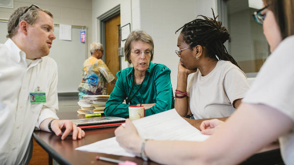 Andrew Falk (from left) works with former volunteer Kelsey Kauffman, Michelle Jones and Natalie Medley in the housing policy class at Indiana Women's Prison in Indianapolis on May 17.