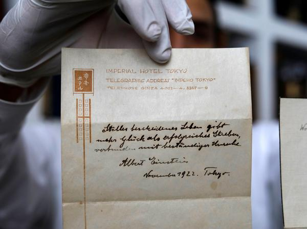 The owner of a Jerusalem auction house holds up a note on happiness written by Albert Einstein in 1922. The note, which Einstein gave to a courier in lieu of a tip, sold for $1.56 million on Tuesday to an anonymous buyer.