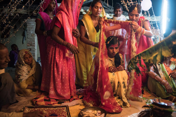 The 14-year-old bride is draped in a red cloth as she waits for the groom to arrive for the wedding rituals in the courtyard of her house.
