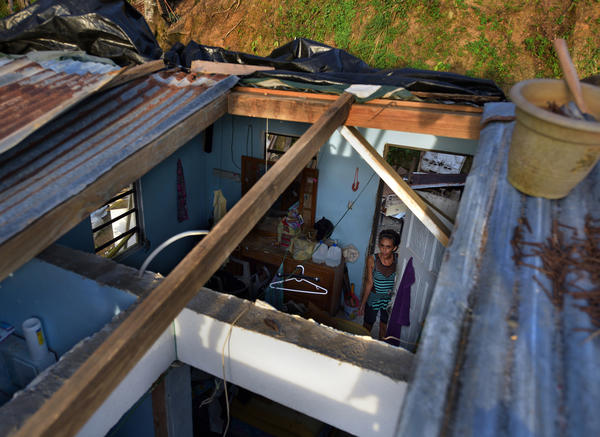 Evangelina Reyes watches as troops and volunteers repair her family's leaking roof.