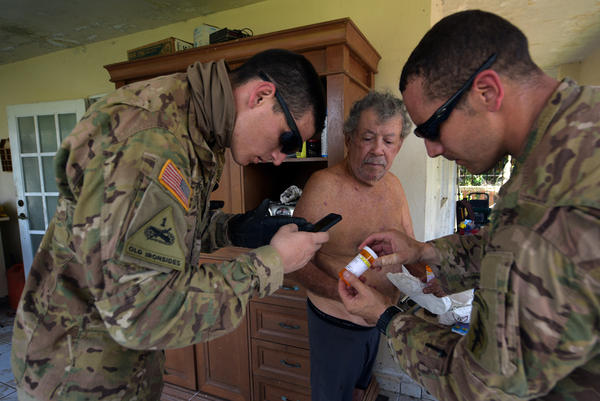 Rescue team members check on a resident's medicine.