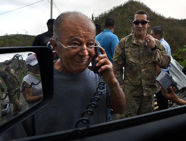 On a satellite phone provided by Santini, Anthony Marrero speaks to his sons in the military at Fort Bragg for first time since the hurricane.