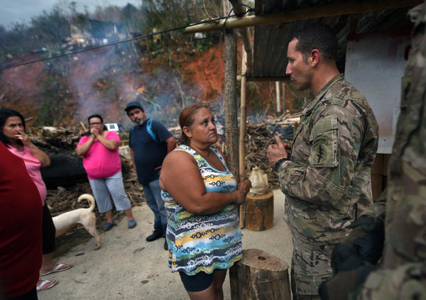 "Santini speaks with hurricane survivors at a collapsed bridge in Utuado. Residents put up a sign saying ""Community of the Forgotten,"" but as troops and volunteers brought food and water to the community, Santini told them they were not forgotten."