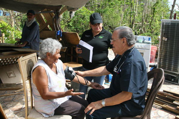 Dr. Eduardo Ibarra checks the blood pressure of Carmen Garcia Lavoy in the Toa Baja area of Puerto Rico. He's been making house calls in the area with nurse Erika Rodriguez.